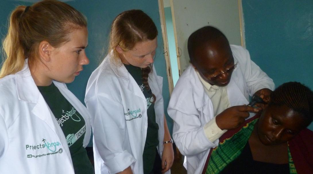Adolescentes observan consulta durante su voluntariado médico en Tanzania.